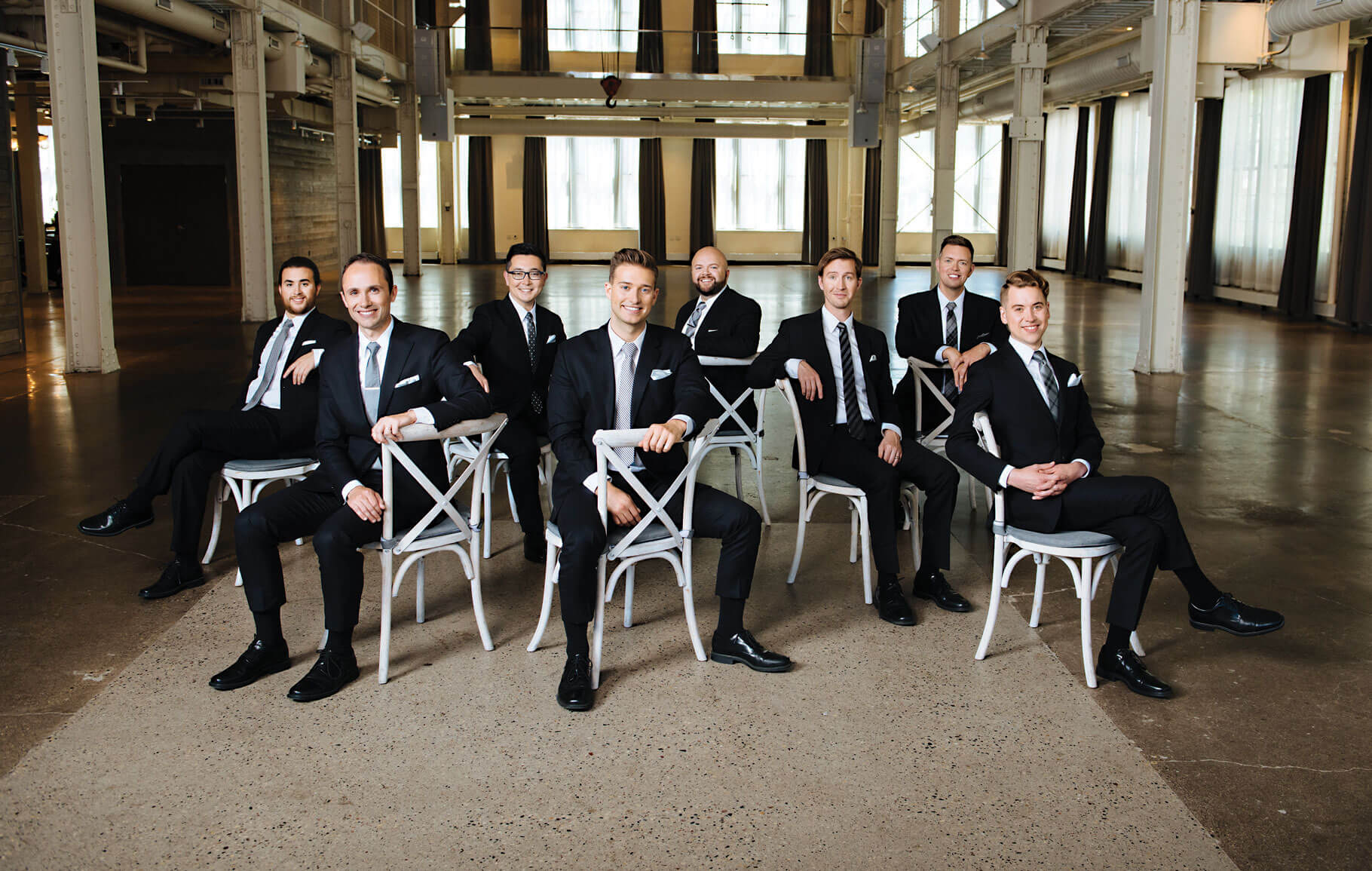 The current 8 singers of Cantus sitting scattered on white chairs in an empty warehouse